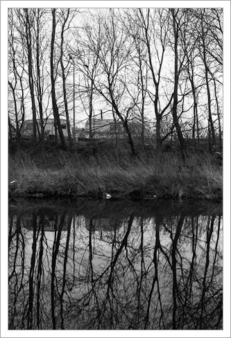 Traveller's caravans and trees reflected in the River Soar