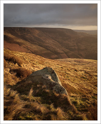 Early morning sun lights up the brown winter hillside in Edale
