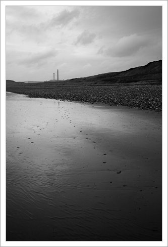 Footprints on an empty beach  with Sellafield in the distance (Black and white), Seascale